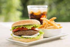 Hamburger with french fries and soft drink. A meat sandwich with salad, fries and iced soda Royalty Free Stock Photography