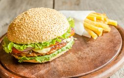 Hamburger and french fries. On the wooden board Stock Photos