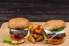Hamburger and french fries on a wooden plate Stock Image
