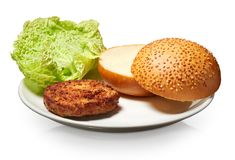 Hamburger, fresh bun with seeds and lettuce on white plate Stock Images