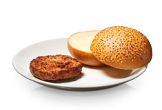 Hamburger and fresh bun with sesame seeds on white plate Stock Images