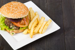 Hamburger. With fresh lettuce, tomato and fries on wooden table stock image