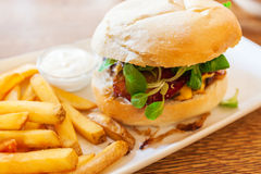 Hamburger with fresh vegetables and French fries. Royalty Free Stock Image
