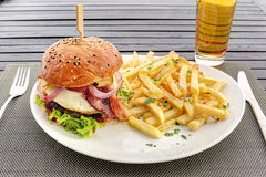 Hamburger with fried egg, bacon and frenchfries on white dish Stock Images