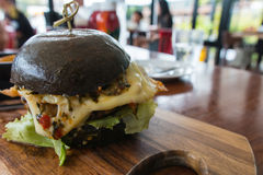 Hamburger with fried egg, pork, cheese, lettuce and black bun Stock Photography