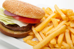 Hamburger and fries. Hamburger with red onion, tomato and lettuce on a sesame seed bun with french fries on a white plate Stock Photo