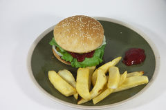 Hamburger with fries. A plate with a hamburger fries and ketchup on it stock photos