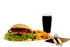 Hamburger and fries. Hamburger with salad, pickle, onions, tomato and French fries.  Studio shot Royalty Free Stock Images