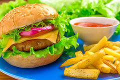 Hamburger and fries. Hamburger, french fries and ketchup on the blue plate Royalty Free Stock Images