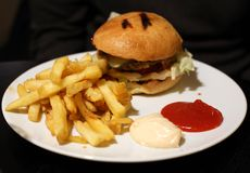 Hamburger, Fries, Ketchup and Mayo on a White Plate. Hamburger and fries photographed on a white plate that`s on a black wooden table. Unhealthy meal full of fat royalty free stock image