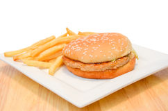 Hamburger with fries on white plate. Royalty Free Stock Images