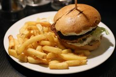 Hamburger and Fries on a White Plate. Hamburger and fries photographed on a white plate that`s on a black wooden table. Unhealthy meal full of fat and calories stock photo