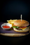 Hamburger with fries on wooden Board. Hamburger with fries on a round wooden Board on black background with ketchup stock photos