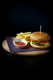 Hamburger with fries on wooden Board. Hamburger with fries on a round wooden Board on black background with ketchup royalty free stock photo