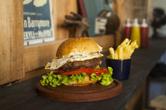 Hamburger with fries on wooden table Royalty Free Stock Photography