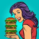 Hamburger géant Femme affamée mangeant des aliments de préparation rapide Image stock