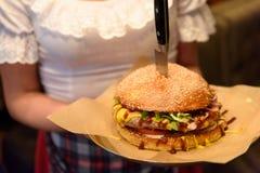 Hamburger gedient von der Kellnerin Lizenzfreie Stockfotos