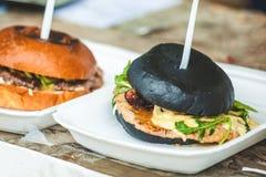 Hamburger gegrillt mit schwarzem Brötchen stockbilder