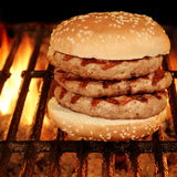 Hamburger grande caseiro na grade flamejante quente do BBQ Fotos de Stock