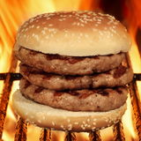 Hamburger grande caseiro na grade flamejante quente do BBQ Imagens de Stock Royalty Free