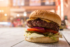 Hamburger on gray wooden surface. Side view of a burger Stock Image