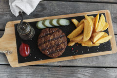 Hamburger grelhado com batatas e molho conservado do pepino foto de stock royalty free