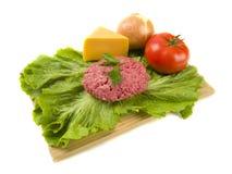 Hamburger grezzo con le guarnizioni Fotografie Stock Libere da Diritti