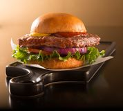 Hamburger on brioche bun on a black plate. Hamburger half pound of beef on a brioche bun on a black plate stock photography
