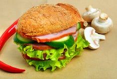 Hamburger with ham, mushrooms, cucumber, salad, chili pepper Stock Photography