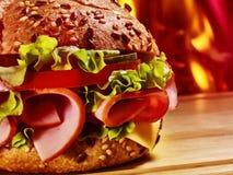 Hamburger with ham on wooden board Royalty Free Stock Photos