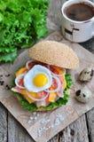 Hamburger, hamburger con manzo arrostito, uovo, formaggio, bacon e verdure Immagine Stock