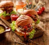 Hamburger, hamburgueres caseiros com os bolos grelhados com adição de adição de costoleta da carne, alface, tomate, pepino conser foto de stock