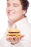 Hamburger in hand of a young chubby man Royalty Free Stock Images