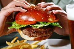 Hamburger in handen Royalty-vrije Stock Afbeeldingen