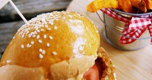 Hamburger het Frans met gebraden gerechten in emmer op lijst wordt gehouden die stock footage