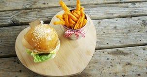 Hamburger het Frans met gebraden gerechten in emmer op lijst wordt gehouden die stock video