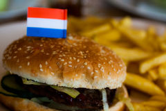 Hamburger holland. Hamburger with the flag of Holland in it and Fries on the background Royalty Free Stock Photos