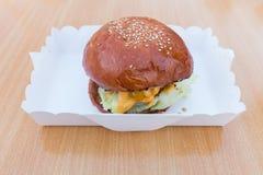 Hamburger im Kasten auf Holztisch Hintergrund Stockfotos