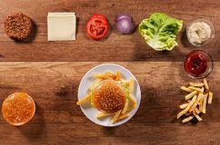 Hamburger ingredients on wooden table with an assembled burger i Royalty Free Stock Photos