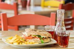 Hamburger of Italian bread with a big steak .Grafin and two glasses of wine. In the tavern in Greece stock photos