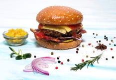 Hamburger juteux de boeuf à l'oignon, lard, concombre sur un fond blanc image stock