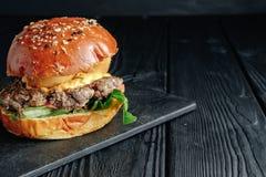 Hamburger juteux fait maison sur le conseil en bois foncé images stock