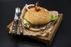 Hamburger juteux frais américain classique avec le poulet et jambon sur un plateau en bois avec de la sauce chili épicée Belle ph image libre de droits