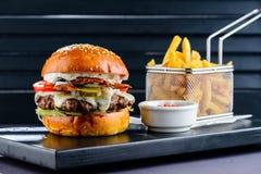 Hamburger juteux savoureux avec des pommes frites dans le café images libres de droits