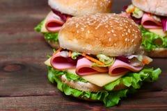 Hamburger kanapka z kiełbasą, serem i warzywami na drewnianym tle, zdjęcie stock