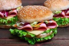 Hamburger kanapka z kiełbasą, serem i warzywami na drewnianym tle, Zdjęcia Stock