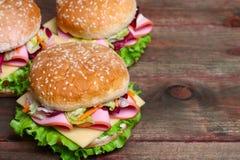 Hamburger kanapka z kiełbasą, serem i warzywami na drewnianym tle, obraz royalty free
