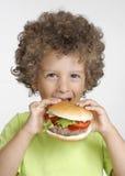 Hamburger kid. Little kid holding a big hamburger,eating hamburger Royalty Free Stock Photography