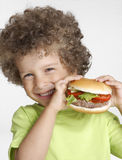 Hamburger kid. Little kid holding a big hamburger,eating hamburger Stock Photo