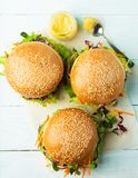 Hamburger léger des verts de légumes frais sur un fond bleu Le concept de la nourriture saine végétale Disposition plate images stock
